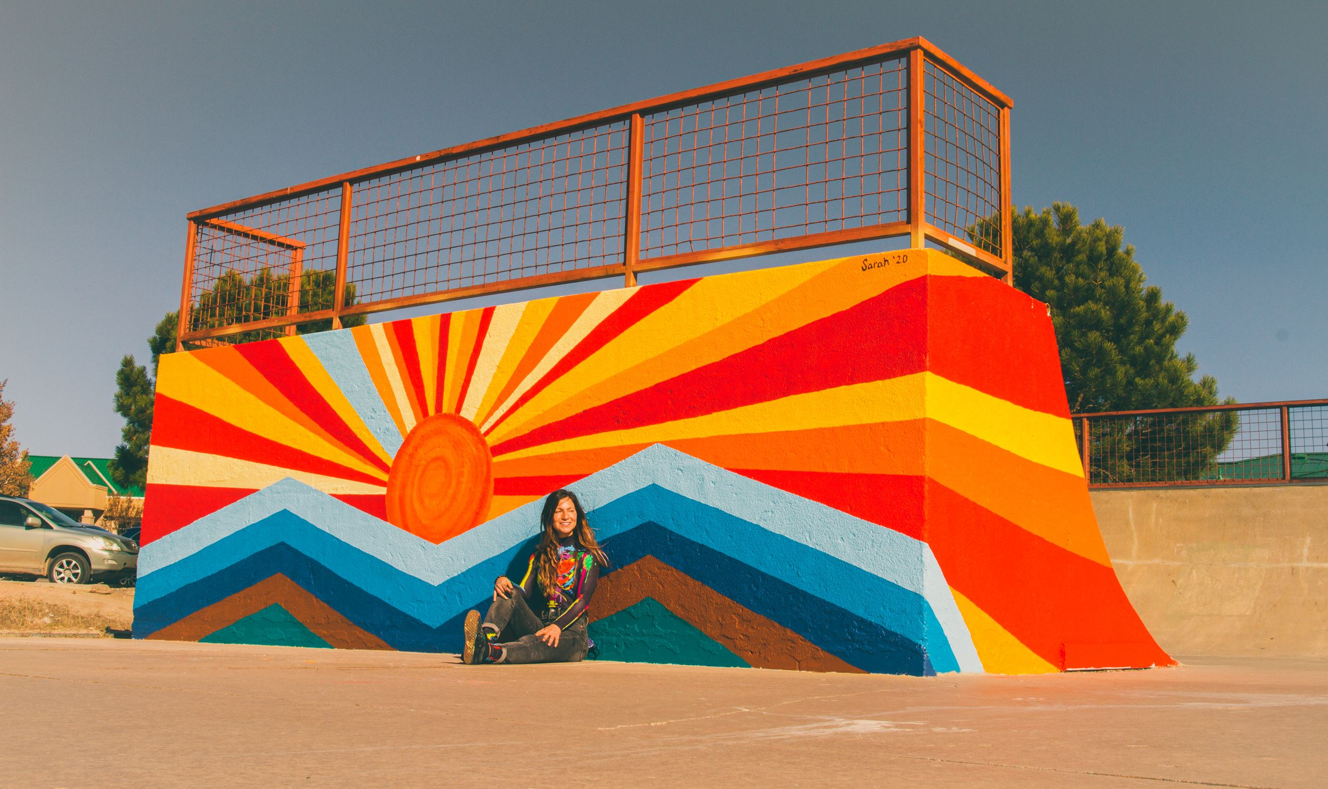 Woman sitting in front of wall painted with sunrise